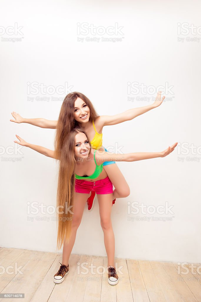 Happy girl piggybacking her friend and gesturing like an airplan stock photo