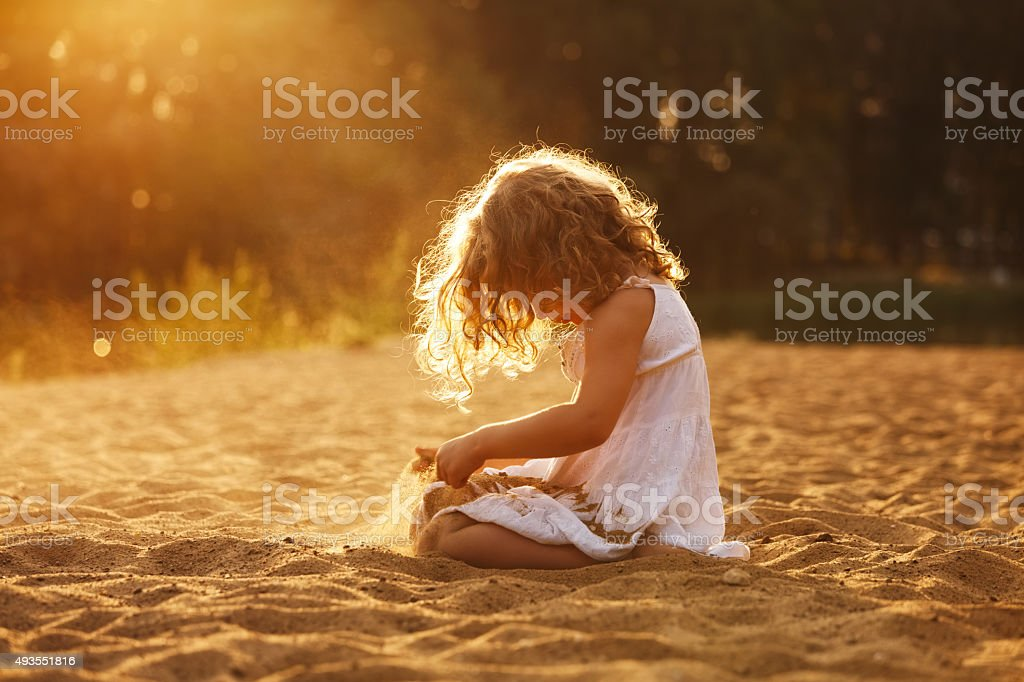 Happy girl playing in the sand stock photo