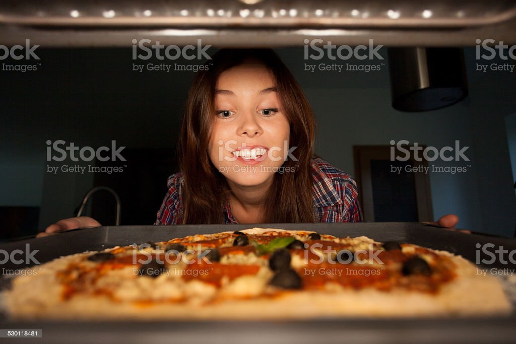 Happy girl putting pizza into oven stock photo
