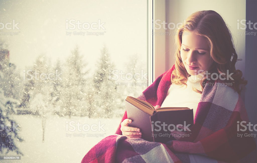 happy girl reading book by the window in winter stock photo