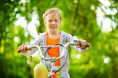 Happy girl riding a bicycle in summer park