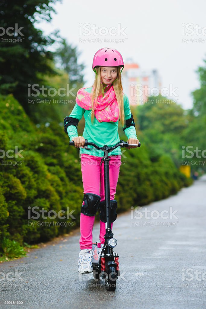 Happy girl riding on electric scooter outdoor stock photo