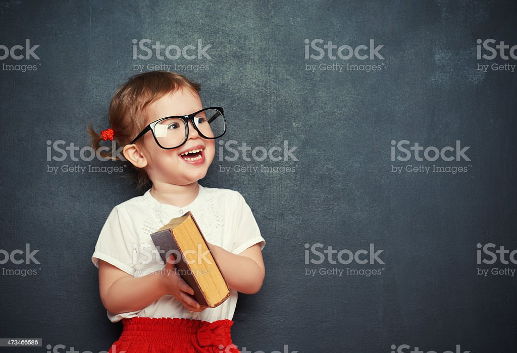 happy  girl schoolgirl with book from blackboard stock photo