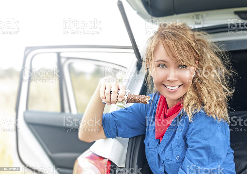 Happy girl sitting in car and holding chocolate. royalty-free stock photo