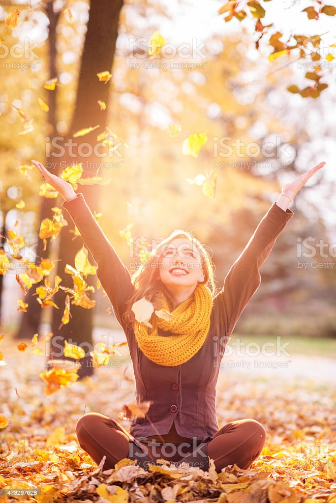 Happy girl sitting in lotus position and throwing autumn leaves. stock photo