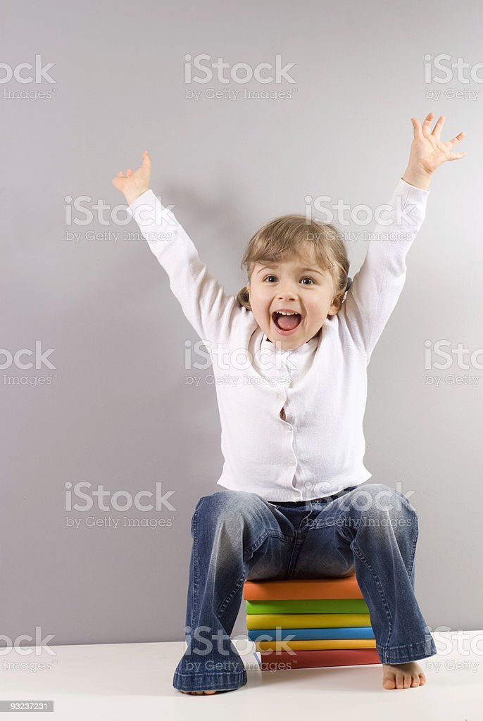 Happy girl sitting on books royalty-free stock photo