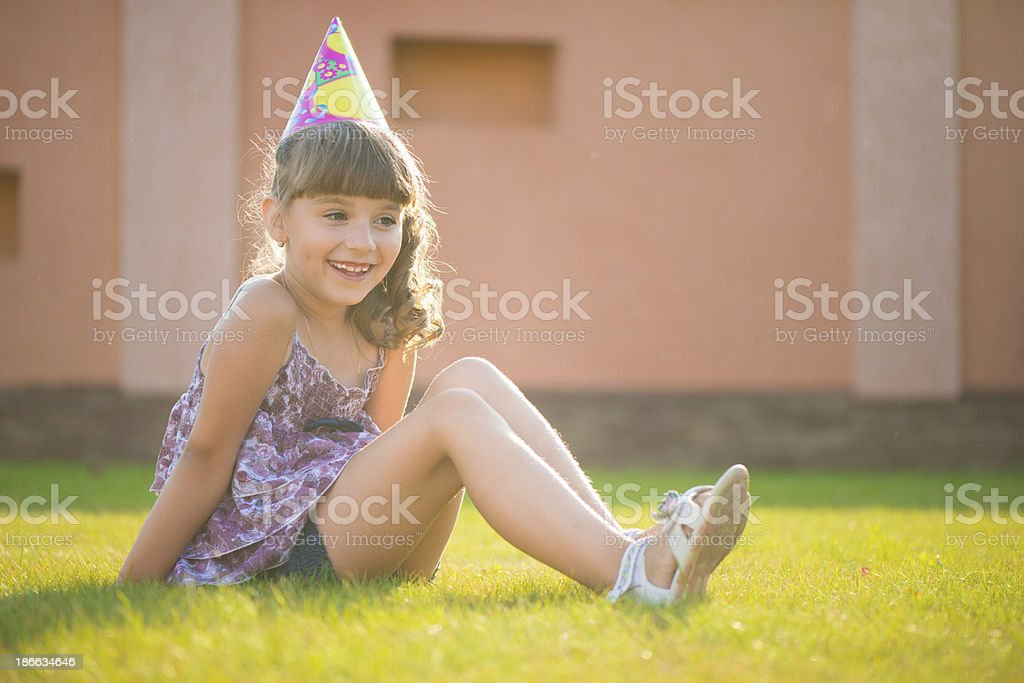 Happy girl sitting on green gras at birthday party royalty-free stock photo