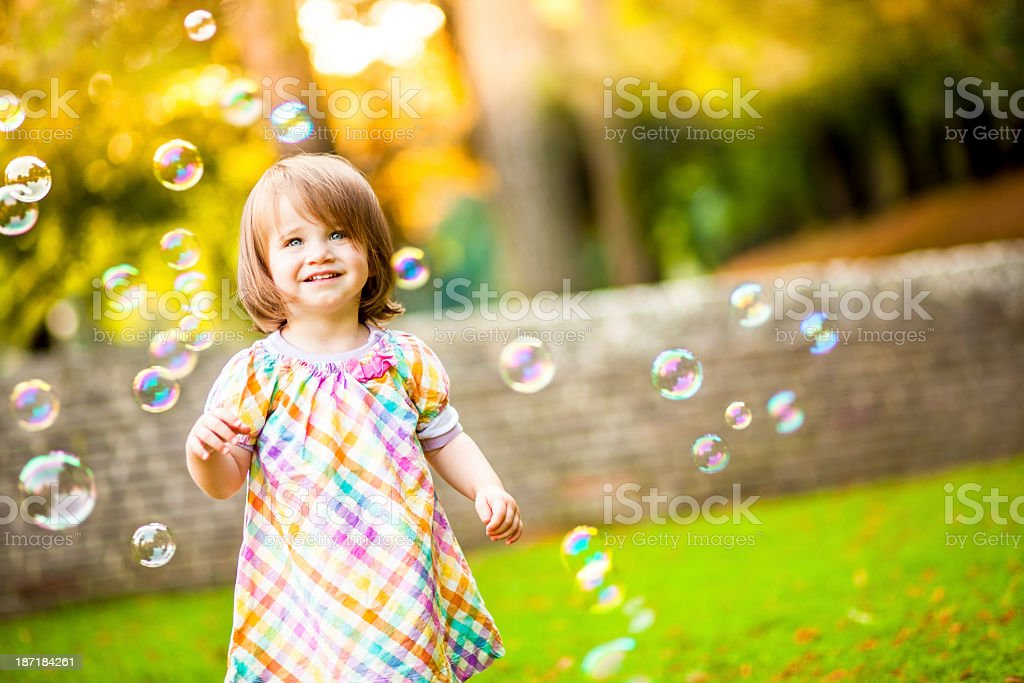 Happy Girl Standing Around Bubbles stock photo