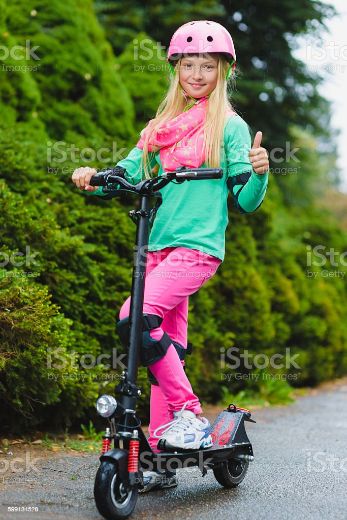 Happy girl standing on electric scooter outdoor stock photo