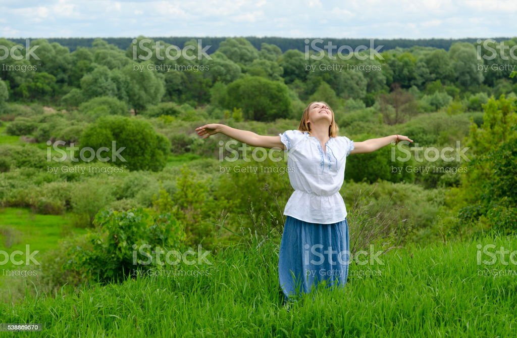 Happy girl stands on field and looks up at sky stock photo