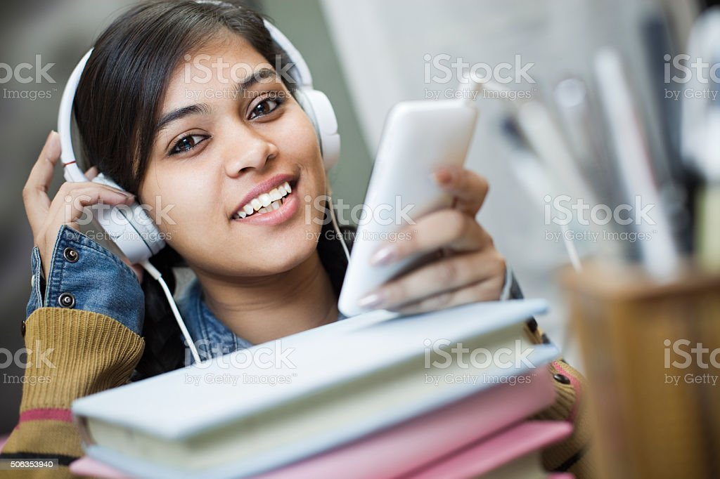 Happy girl student listening music through headphones and smartphone. stock photo