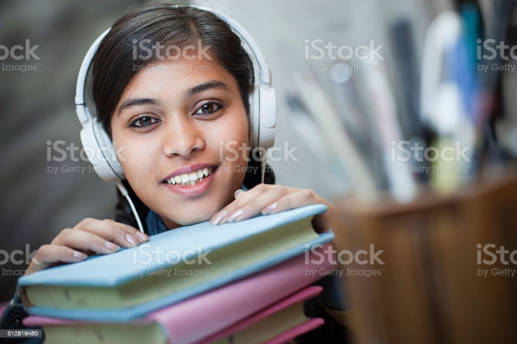 Happy girl student listening music through headphones on study table. stock photo