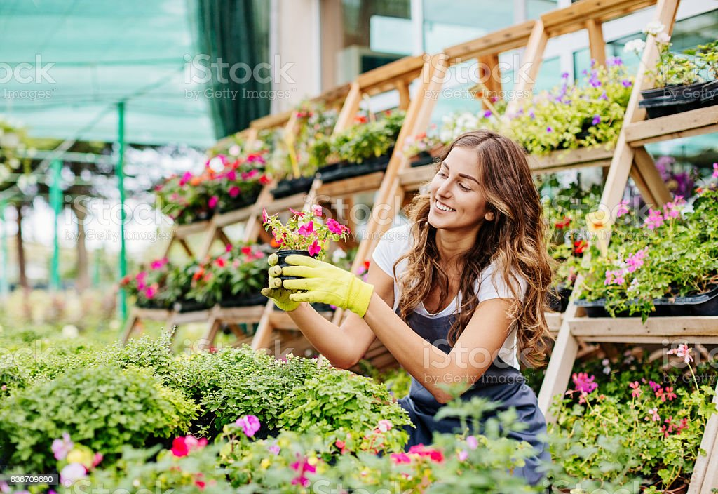 Happy girl surrounded with flowers stock photo
