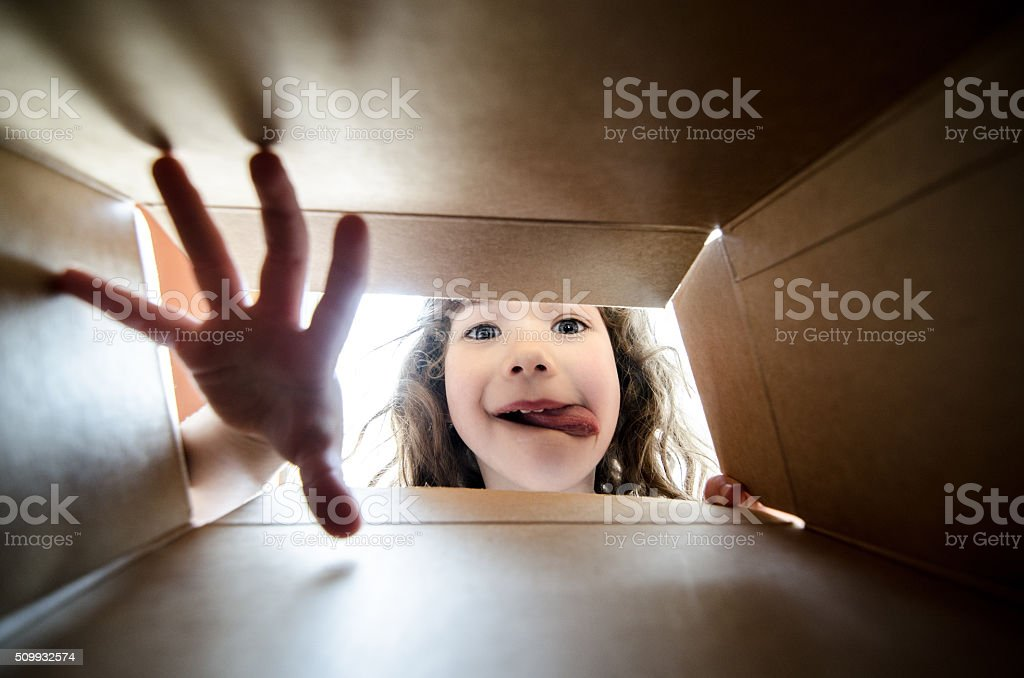 Happy girl taking a cookie in box from inside stock photo