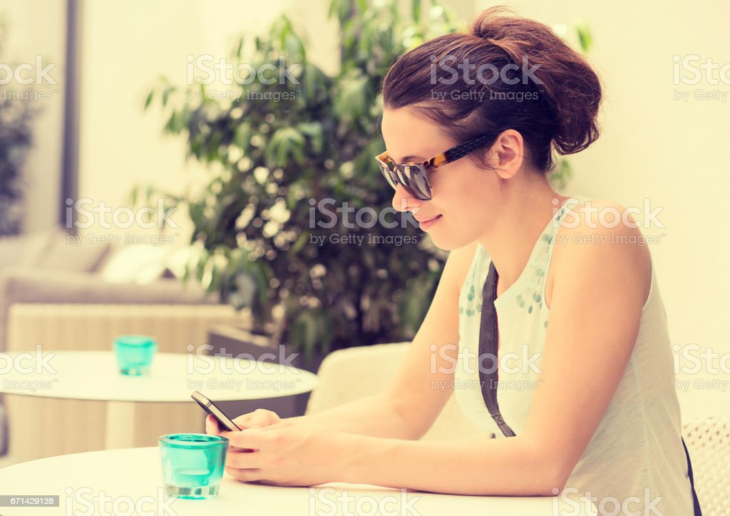 Happy girl texting on the smart phone in a hotel restaurant terrace stock photo