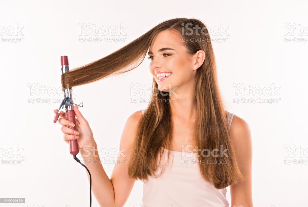 happy girl twists hair curling on iron stock photo