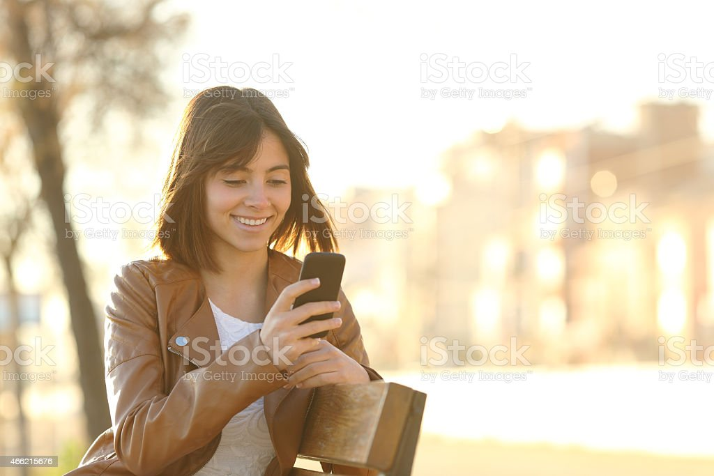 Happy girl using a smart phone in a city park stock photo