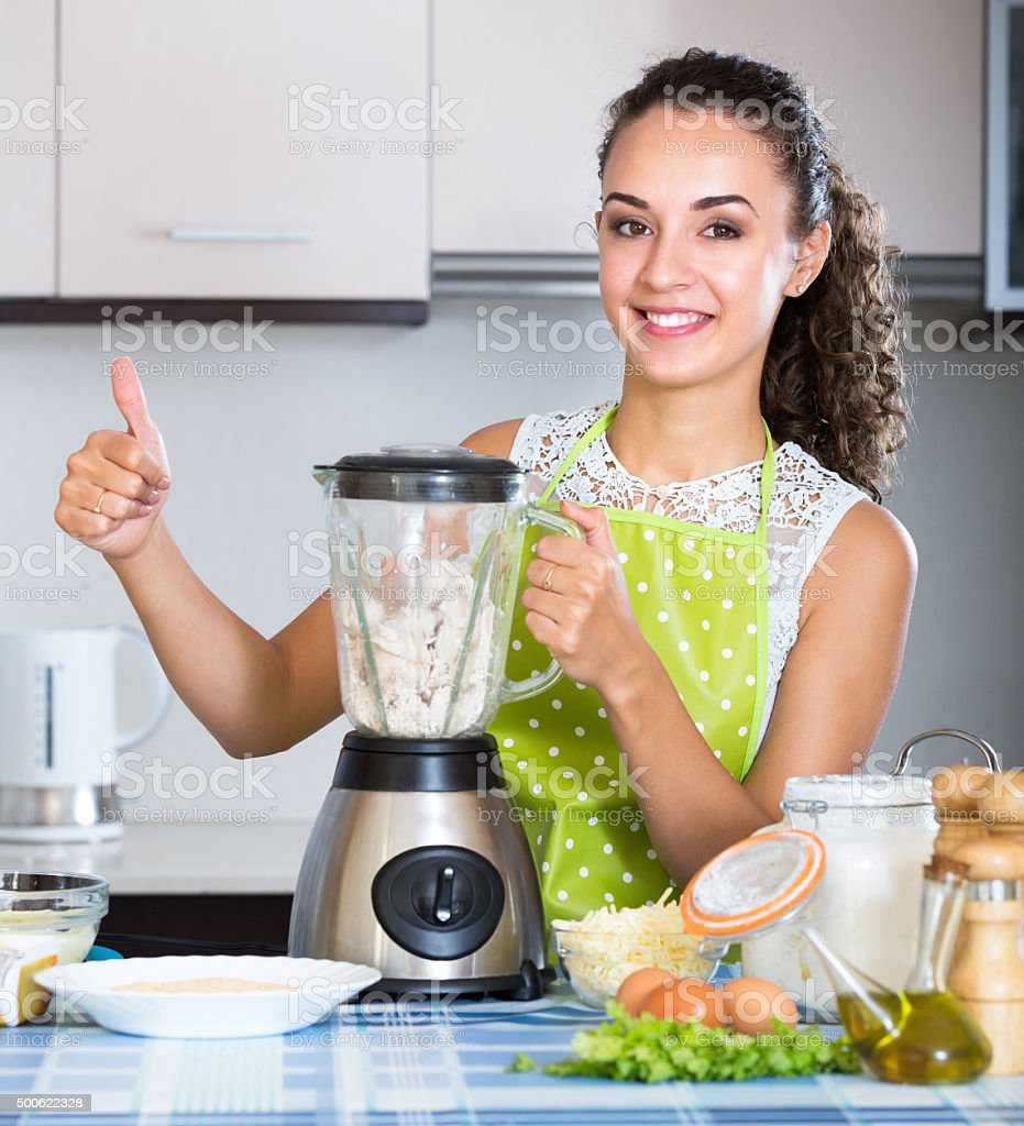 Happy girl using blender and grinding ingredients stock photo