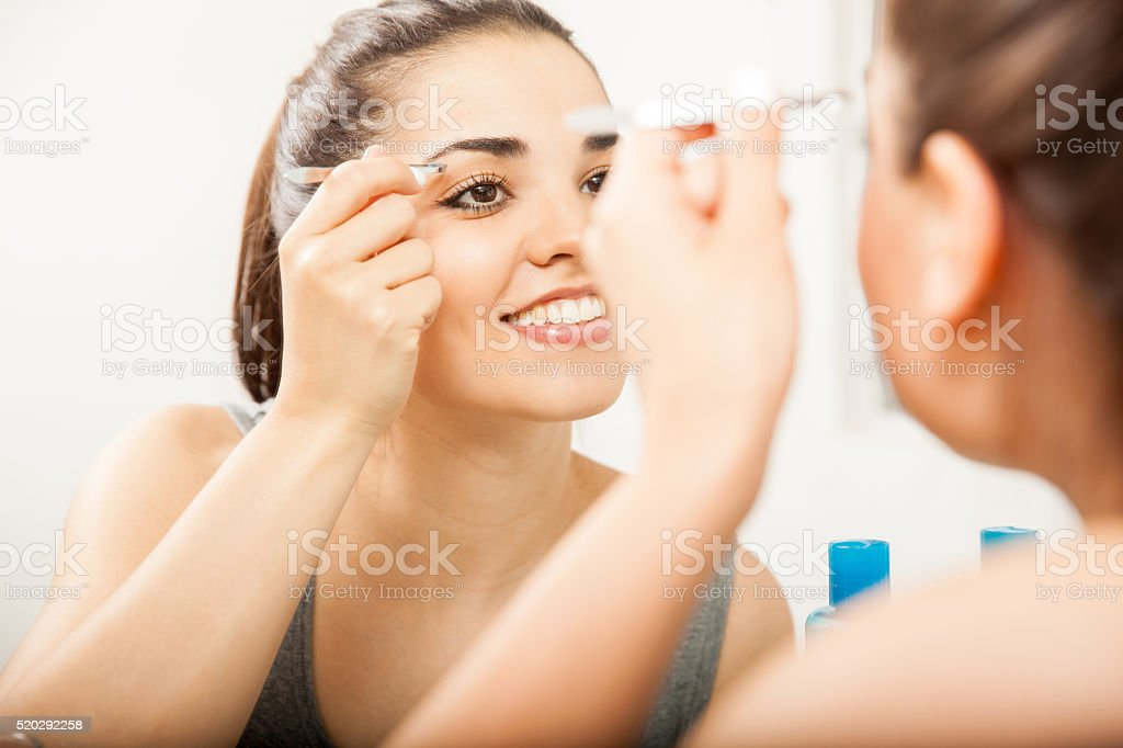 Happy girl using tweezers on her eyebrows stock photo