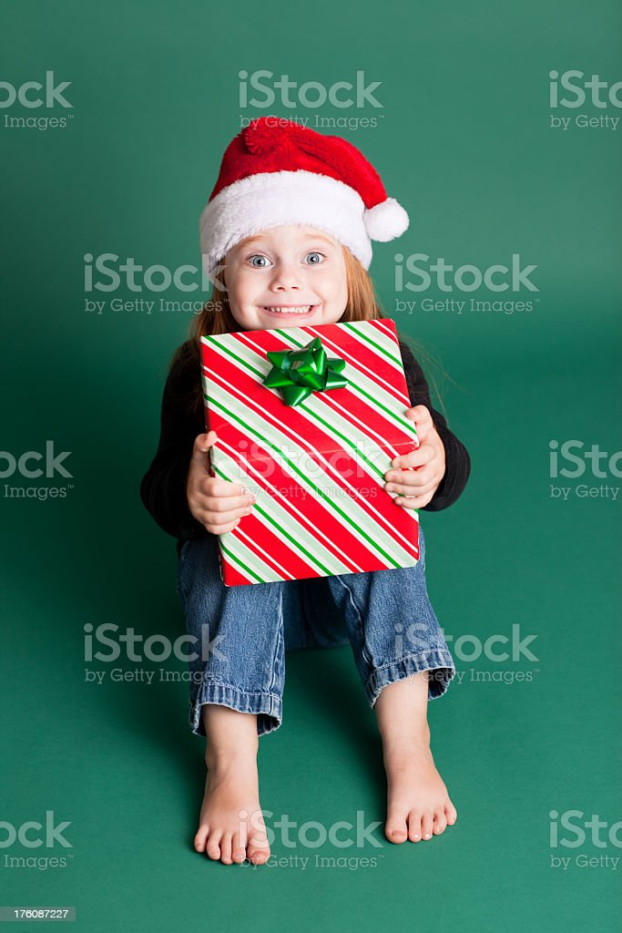 Happy Girl Wearing Santa Hat with Christmas Present royalty-free stock photo