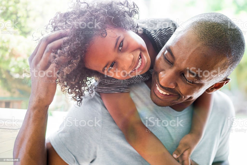 A photo of happy girl with arms around father. Young man is looking...