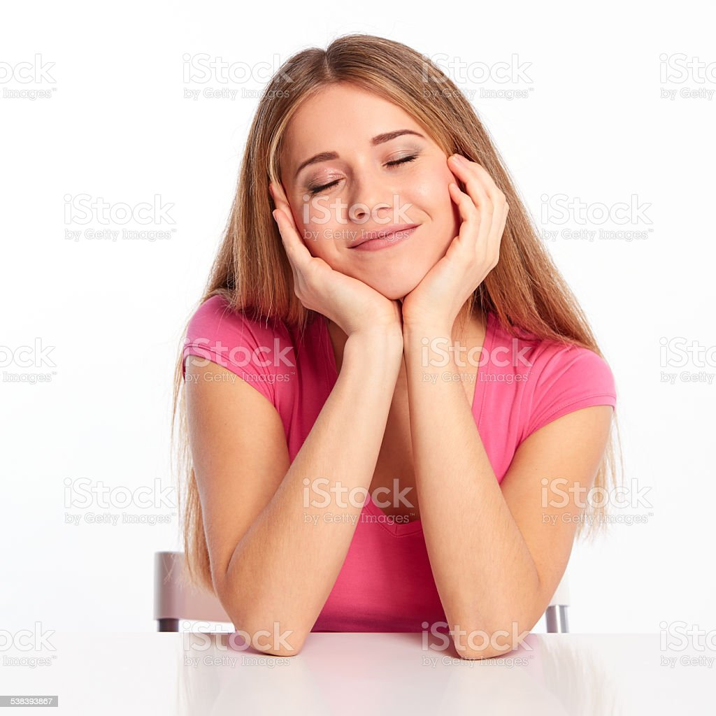 Happy girl with closed eyes behind a table stock photo