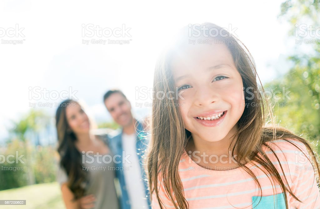 Happy girl with her family at the park stock photo