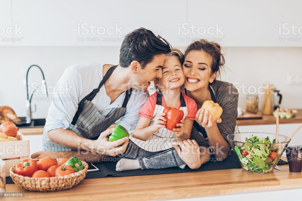 Happy girl with mom and dad in the kitchen stock photo