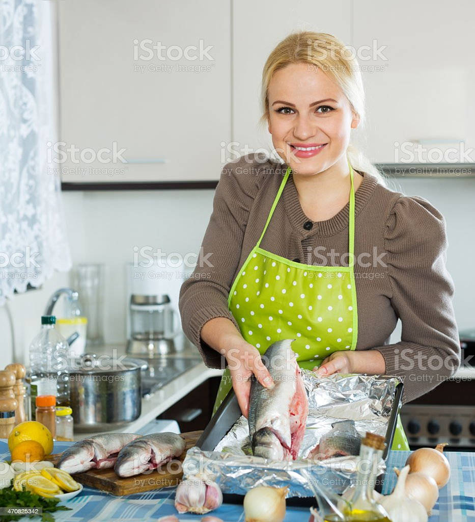 Happy girl with raw fish stock photo