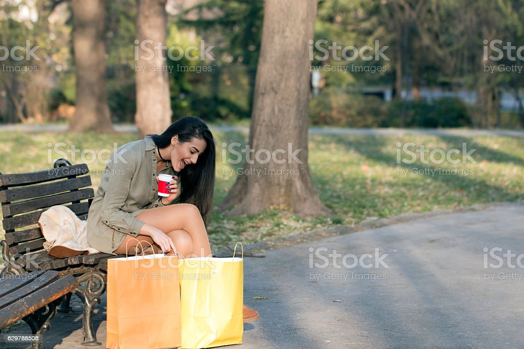 Happy girl with shopping bags in the park stock photo