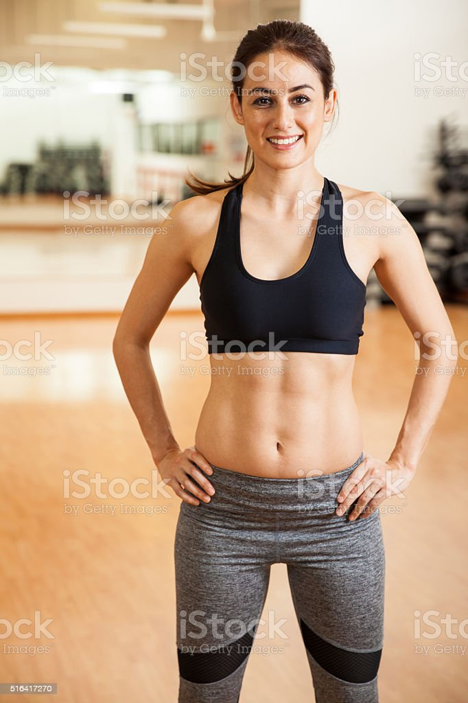 Happy girl with toned abs in a gym stock photo
