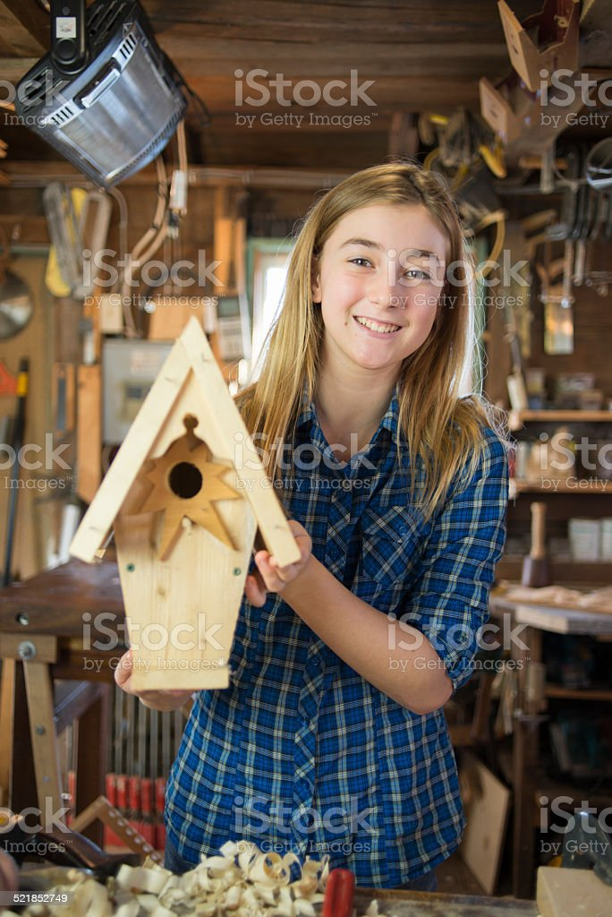 Happy Girl With Wooden Birdhouse Project stock photo