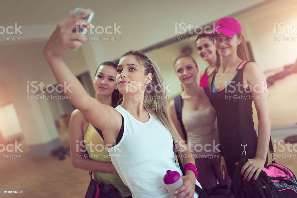 Happy Girlfriends Group Taking Selfie in Gym after Exercise stock photo