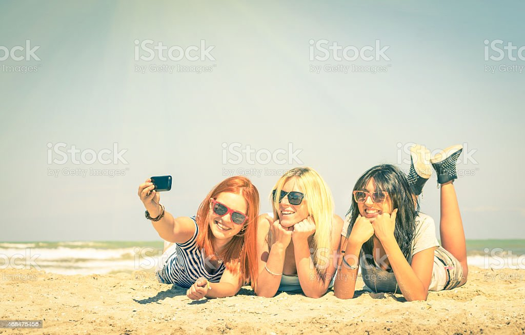 Happy girlfriends having fun and taking selfie at beach stock photo