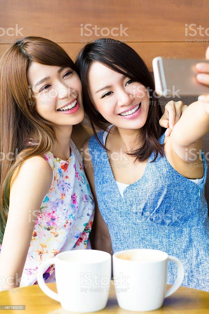 happy girlfriends taking a selfie in coffee shop stock photo