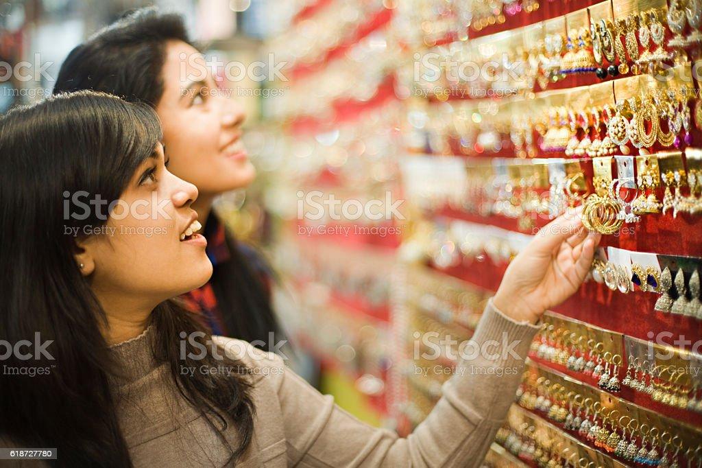 Happy girls buying earrings in jewelry shop before festival. stock photo