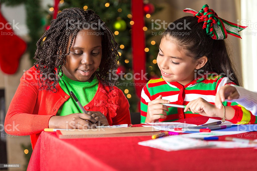 Happy girls drawing together at Christmastime stock photo