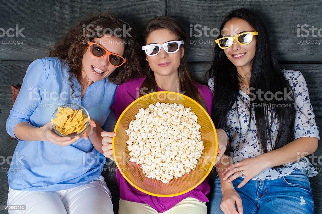 Happy girls eating movie snacks stock photo