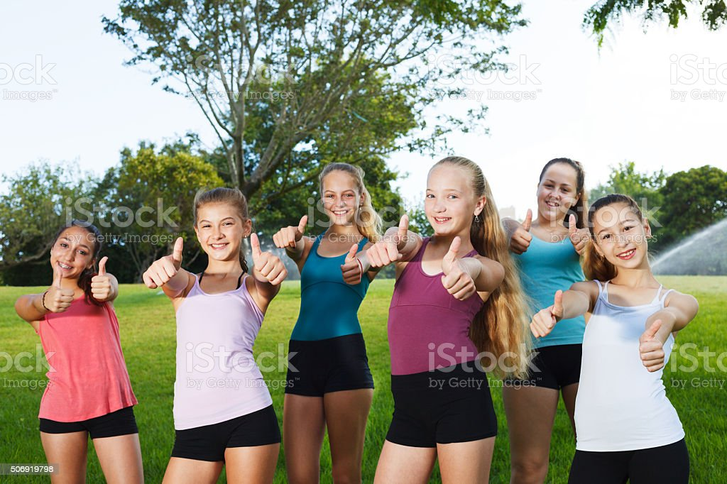 Happy girls holding thumbs up stock photo