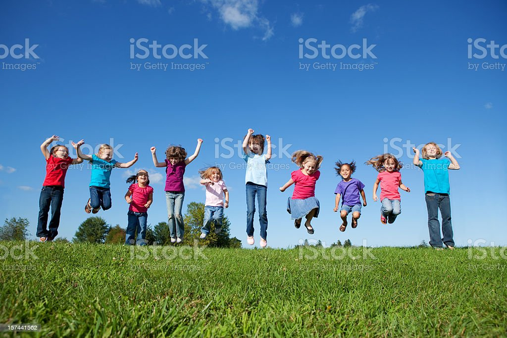 Happy girls jumping outdoors royalty-free stock photo