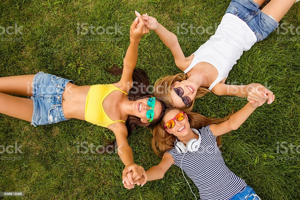 happy girls lying on grass and holding hands stock photo