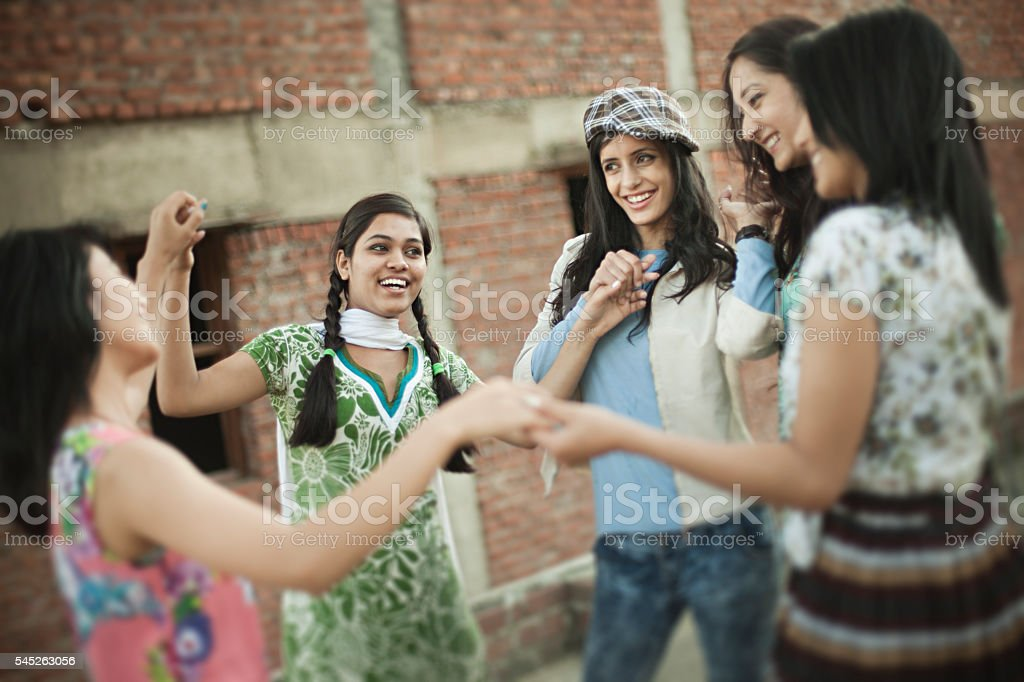 Happy girls of different ethnicity playing by hand in hand. stock photo