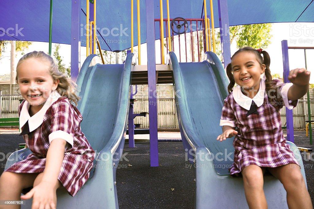 Happy girls on slippery dip stock photo