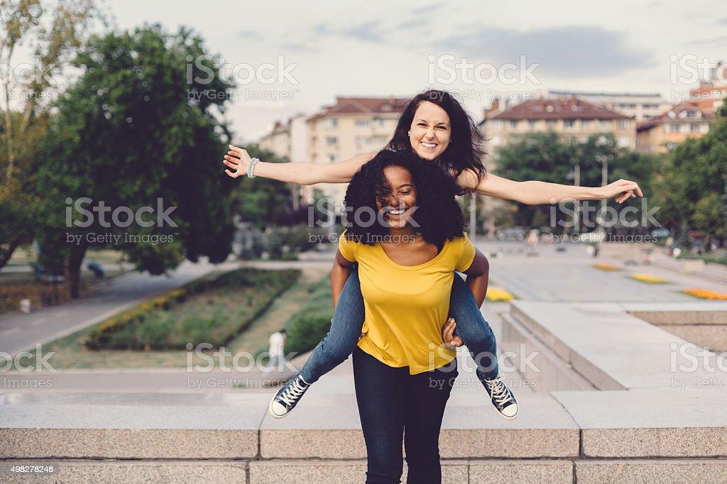 Happy girls piggyback in the park stock photo