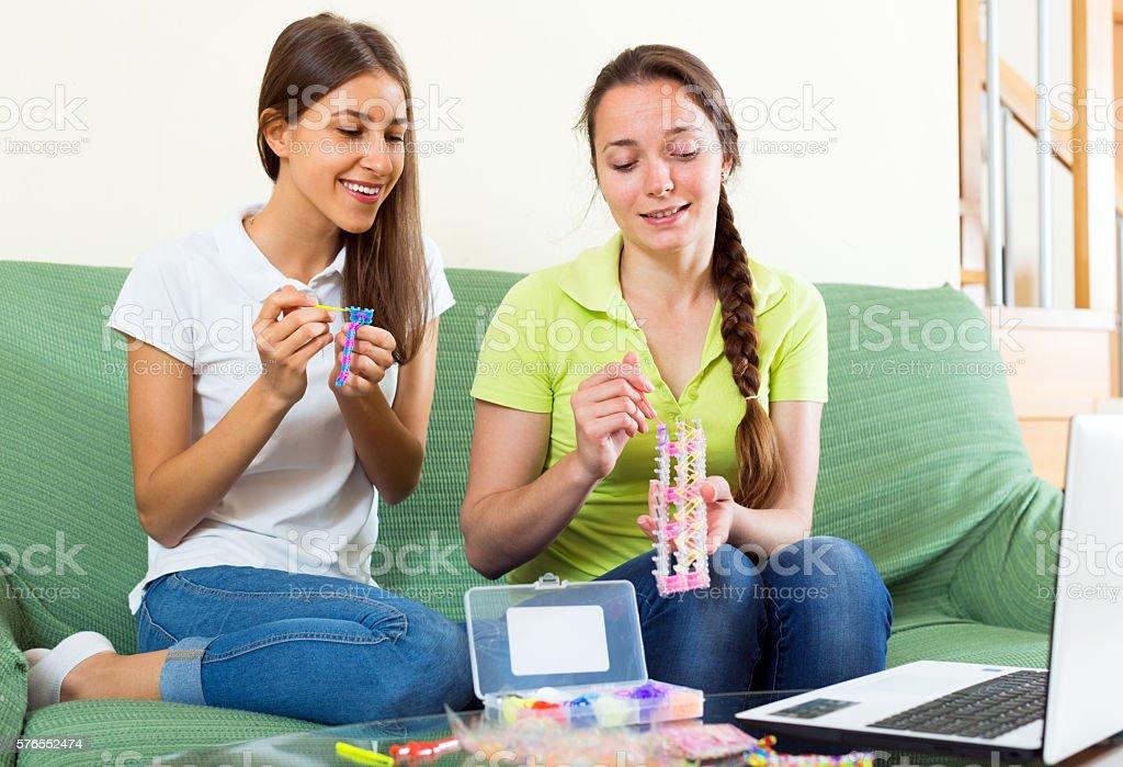 Happy girls plaiting accessories stock photo