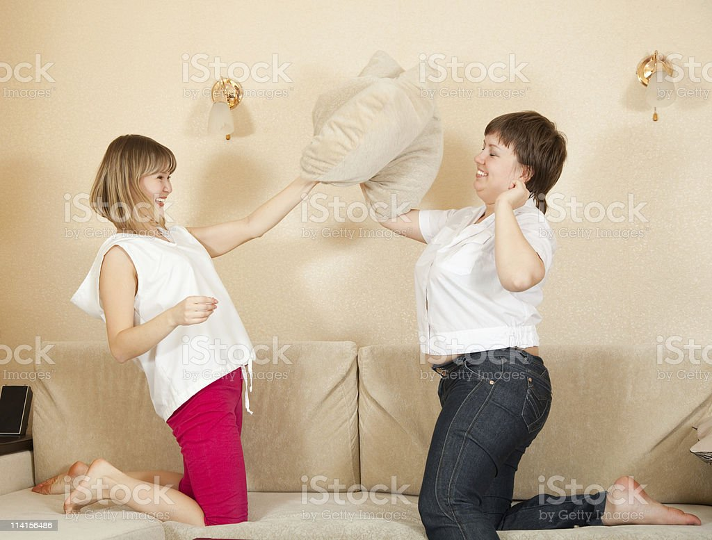 Happy girls playing with pillows royalty-free stock photo