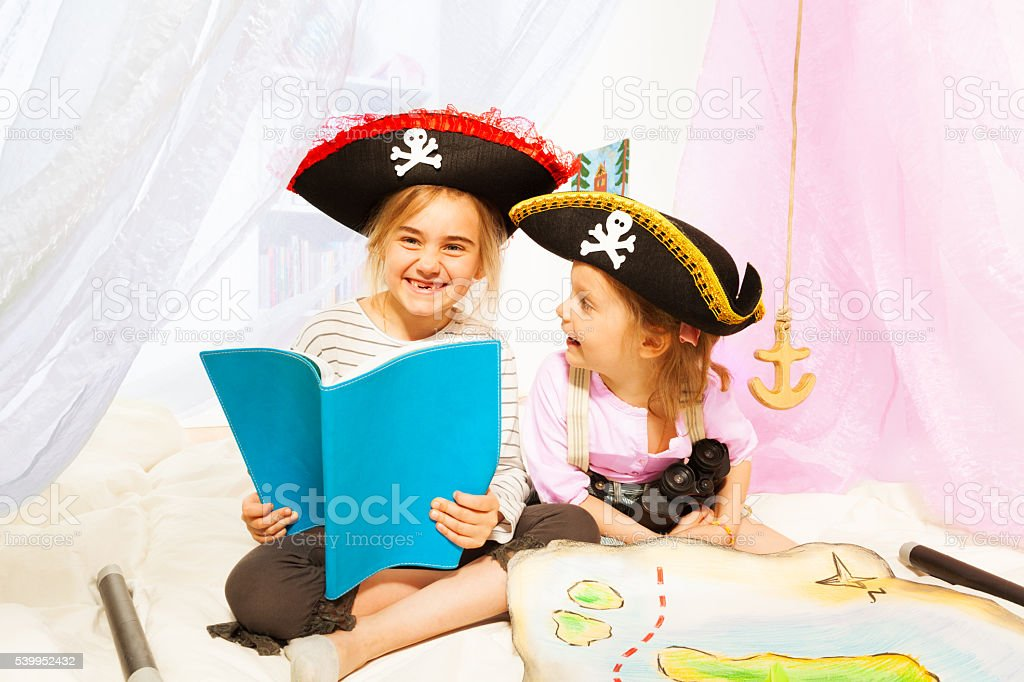 Happy girls reading book about pirate's treasures stock photo