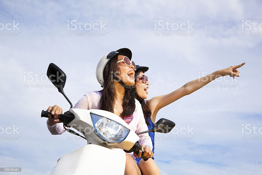 happy girls riding scooter stock photo