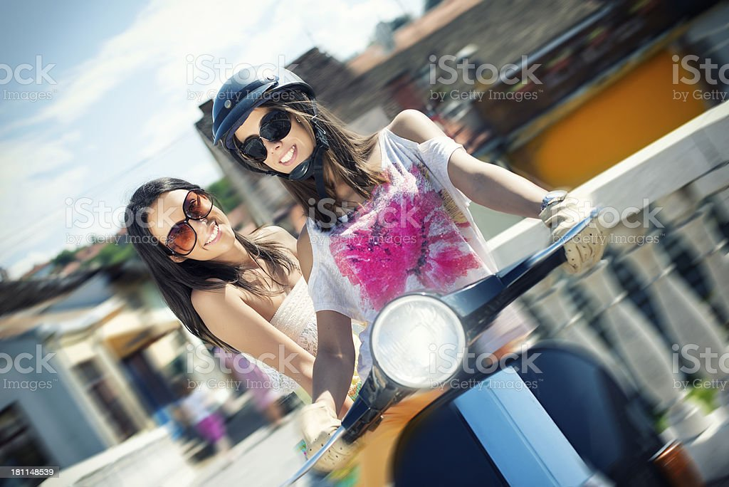 Happy girls riding scooter royalty-free stock photo