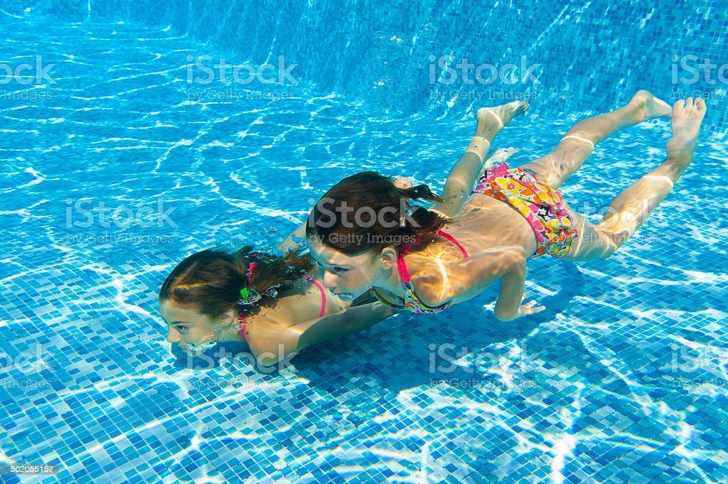 Happy girls swim underwater in pool and having fun stock photo